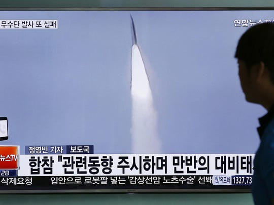 FILE - In this May 31, 2016, file photo, a man watches a TV news program reporting about a powerful new Musudan mid-range missile launch of North Korea, at the Seoul Train Station in Seoul, South Korea. North Korea said Wednesday that it was examining operational plans for attacking Guam, an angry reaction to U.N. punishment for recent North Korean intercontinental ballistic missile tests and a U.S. suggestion about preparations for possible preventive attacks to stop the North's nuclear weapons program. (AP Photo/Lee Jin-man, File)