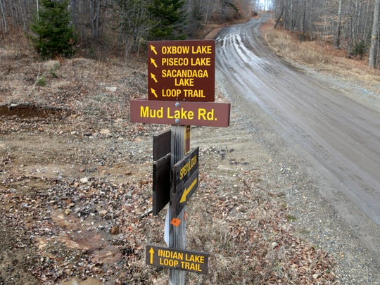 Signs give directions to various locales on a seasonal road that is used by snowmobilers during the winter months on Tuesday, Dec. 8, 2015, in Lake Pleasant, N.Y. Some Northeasterners are beginning to wonder if a white Christmas may just be a dream, and business owners who rely on snow are starting to worry if warm weather could lead to a nightmare winter.