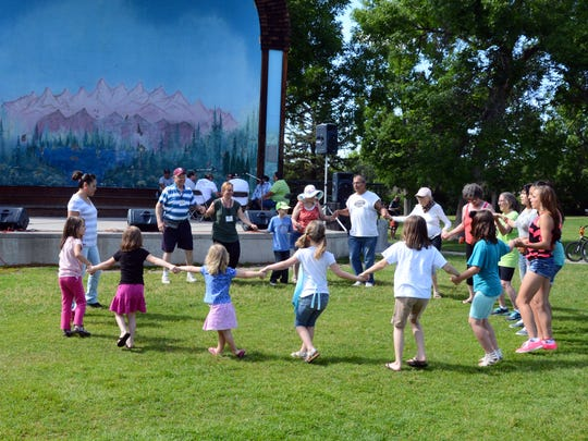 Children participate in the Lewis and Clark Festival Circle Dance near the Gibson Park band shell.