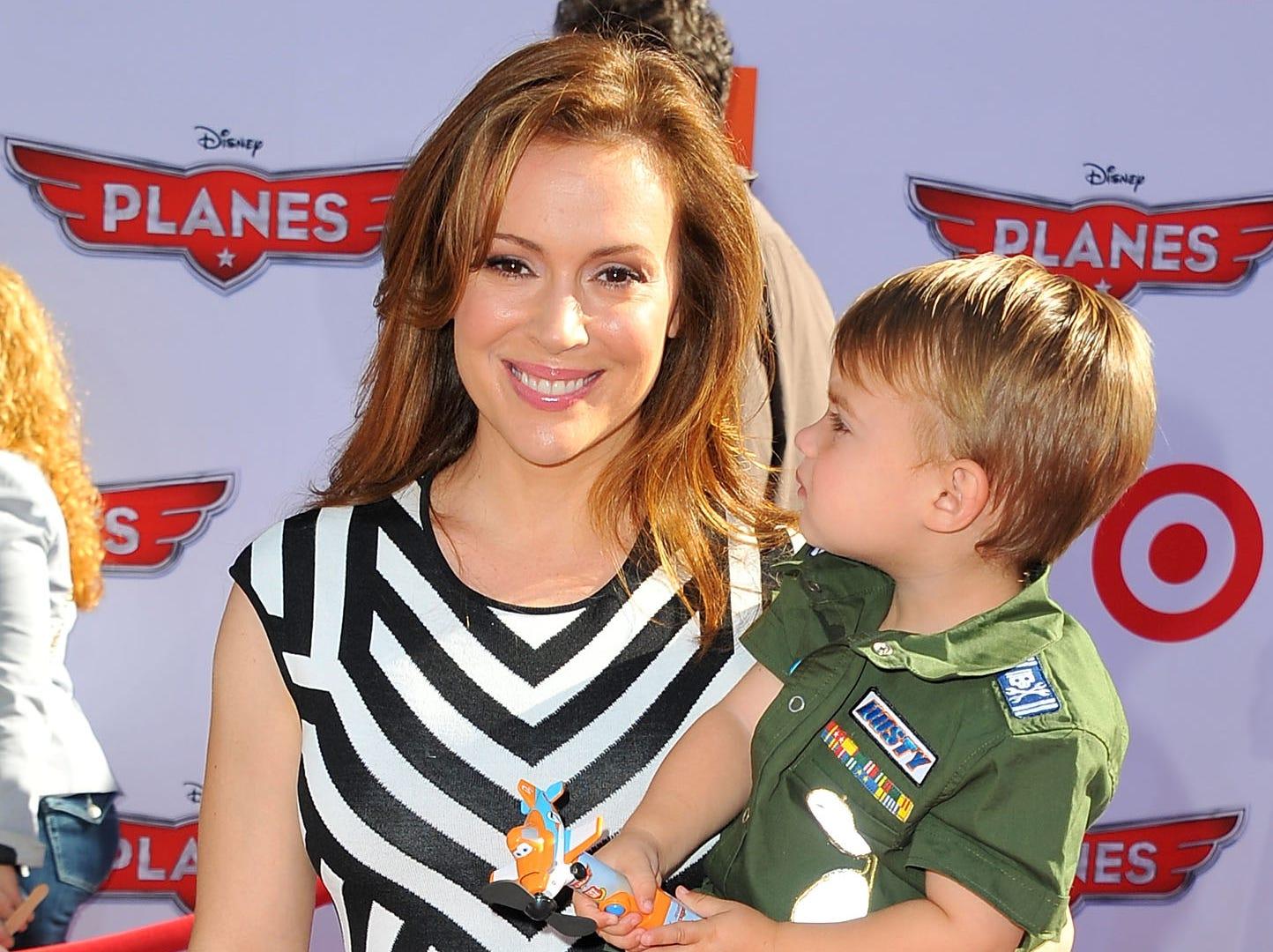 Alyssa Milano, along with son Milo Thomas Bugliari, shows off her love of stripes at the 'Planes' premiere.