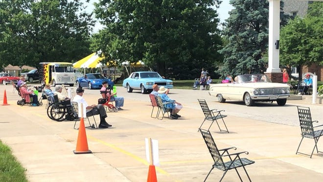 Cars pass by residents of Wesley Village during a Father's Day parade at the Village.