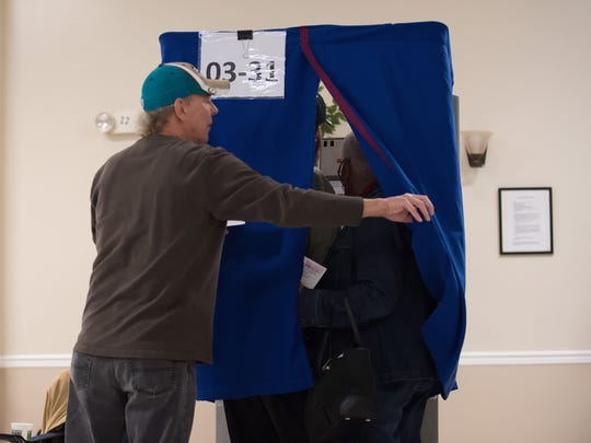 Peter Ackles, a volunteer machine clerk, helps voters into a voting booth at the Dover Elks Lodge No. 1903 in Dover on Election Day last year.