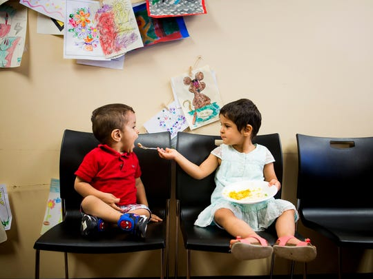 Ghalia Alhamoud feeds hummus to her her brother, Yousif, at an Eid al-Fitr celebration at the Catholic Charities offices. Eid al-Fitr marks the end of Ramadan fasting.
