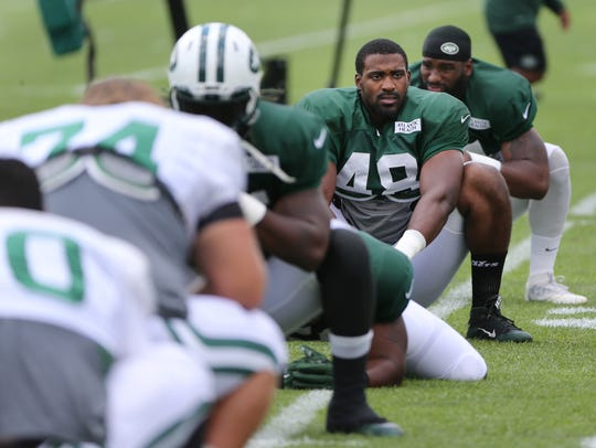 Jordan Jenkins of the Jets stretches during practice