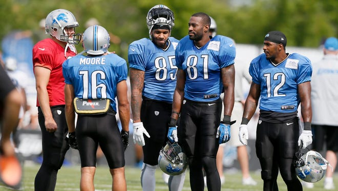 Detroit Lions quarterback Matthew Stafford, left, talks with players left to right, Lance Moore, Eric Ebron, Calvin Johnson, and Jeremy Ross as they wait for the next set of drills to start during practice on Friday, August 7, 2015, in Allen Park. Julian H. Gonzalez/Detroit Free Press
