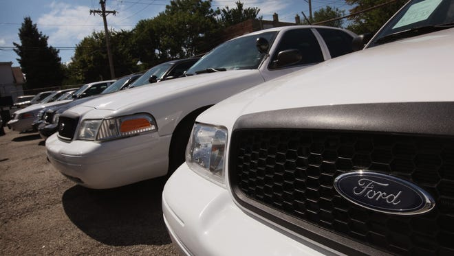 Ford Crown Victorias, once used as police cars, sit in a used car lot September 8, 2011 in Chicago, Illinois.