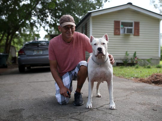 Ray Acker poses with his service dog Luna outside his home in Greenwood Trailer Park Wednesday. Because he has a generator, Acker has opened his door to his neighbors-- a family of five-- since Irma knocked out power in the neighborhood.