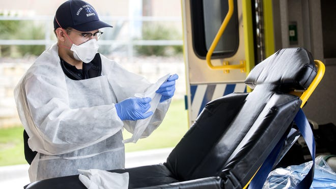 Medic Alex Piwczynski of Austin-Travis County Emergency Medical Services prepares to decontaminate a gurney after transporting a patient to St. David's Hospital in Austin on April 10.
