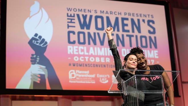 McGowan hugs Tarana Burke (right) the creator of #MeToo, as she was being introduced to the stage during Fighting for Survivors of Sexual Assault in the Age of Betsy DeVos during The Women's Convention at Cobo Center.