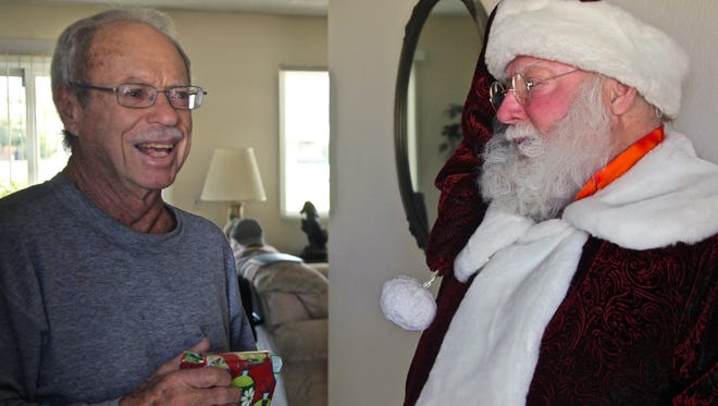 """Palm Desert resident Harry """"Dan"""" Skaglund smiles after receiving a wrapped gift from Bob Elias, Joslyn's Center director of Social Services, on Wednesday, Dec. 23, 2015."""