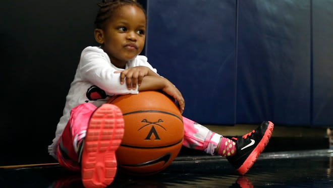 In this Jan. 27 photo, Ngoty, the adopted daughter of Virginia women's basketball coach Joanne Boyle, rests on a basketball as she plays with members of the women's basketball team in Charlottesville.