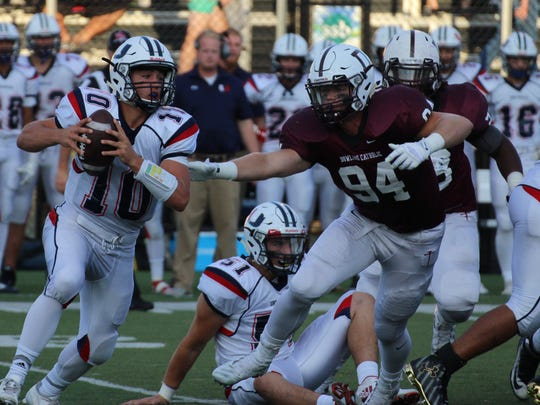 Dowling's John Waggoner (94) chases Urbandale quarterback George Reis in a Class 4A game in 2016.