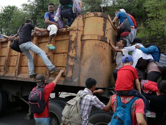 Varios migrantes hondureños se trepan a la caja de