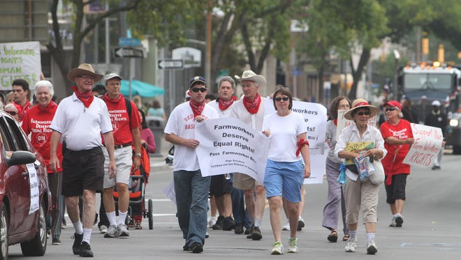 A group marches to support equal rights for farm workers during the Labor Day Parade.