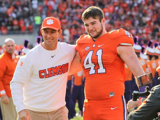 Clemson head coach Dabo Swinney, left, talks with Clemson senior Grant Radakovich during senior day festivities before kickoff on Saturday, November 12 at Memorial Stadium in Clemson.