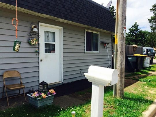The entrance to David Roth's home, seen Tuesday, June 16, 2015, is attached to a restaurant and a fenced-in area with salvage considered by village officials to be a code violation.