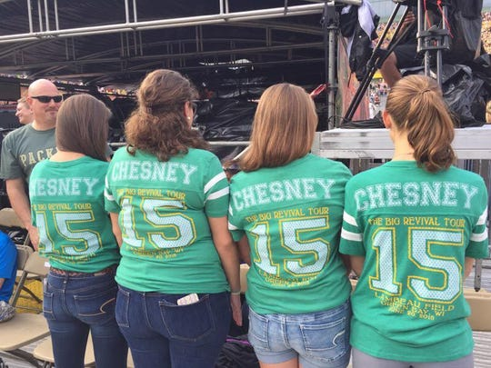 """The daughters of Brad and Debbie Conley of Tennessee, Joe and Sue Morzenti of De Pere and Jeff and Sara Hockers of De Pere show off their matching shirts at Lambeau Field. Brad is the head football coach at Gibbs High School, the same high school Kenny Chesney attended, and is featured in """"The Boys of Fall"""" video."""