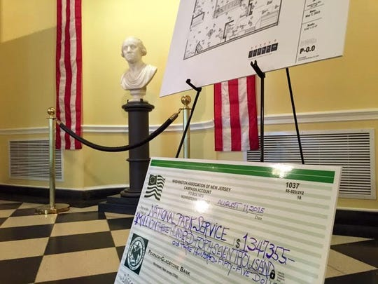 A $1.3 million check rests against plans for the Discover History Center at Washington's Headquarters museum.
