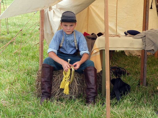Garrett Petruskie, 12, of Colonial Beach, Va., who portrays a Confederate bugler, sits in the heat during the 150 Gettysburg Anniversary National Civil War Re-enactment in 2013.