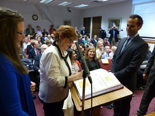 Newly elected commissioners Patty Bordman and Pierre Boutros sign the clerk's Oath of Office book.