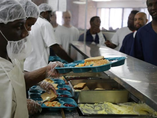 Inmates are served food through the Aramark Correctional Services on Tuesday, June 24, 2014, at the Charles E. Egeler Reception & Guidance Center in Jackson.