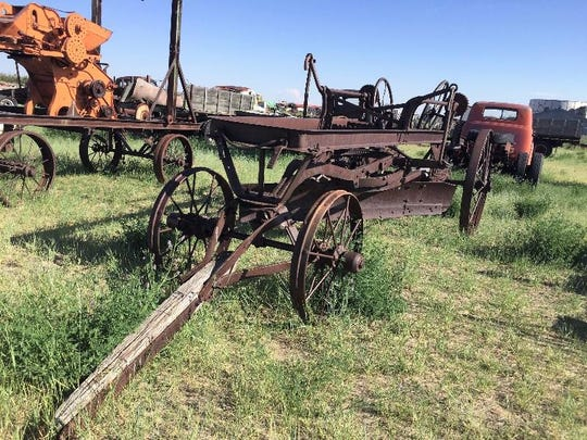 """A wagon used as a road grader at the Rustless in Montana yard east of Cut Bank. The vehicle is marked """"1910."""""""