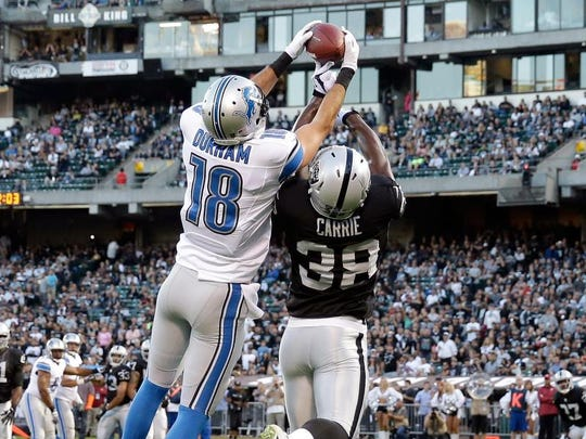Lions wide receiver Kris Durham catches a 4-yard touchdown pass against Raiders cornerback T.J. Carrie during their preseason game on Friday.