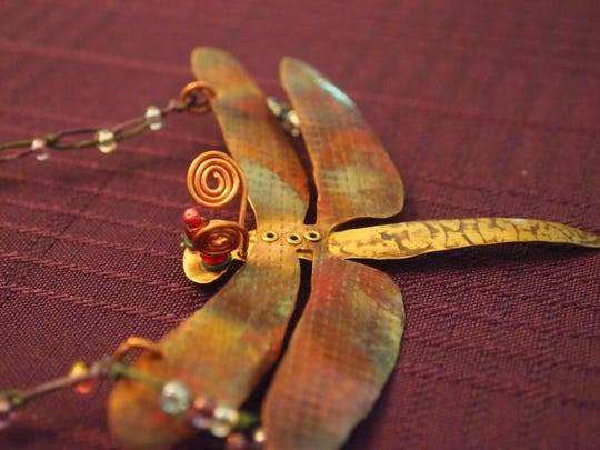 A dragonfly necklace by Kathy Perez.
