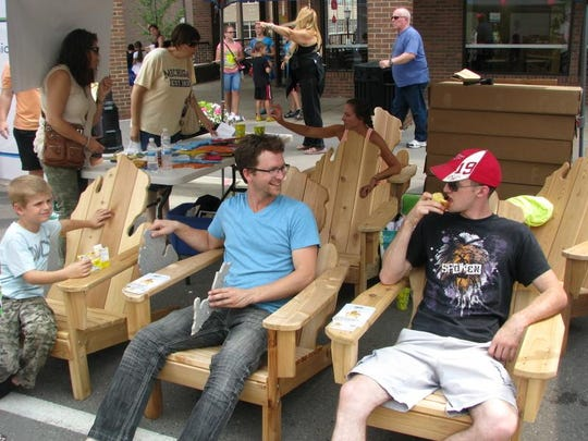 """A couple festival goers try out some of the Michigan-shaped chairs at the Michigan Adirondack Chairs display at the Buy Michigan Now Festival over the weekend. The owners of the company won the festival's """"Up & Coming Entrepreneur Contest."""""""