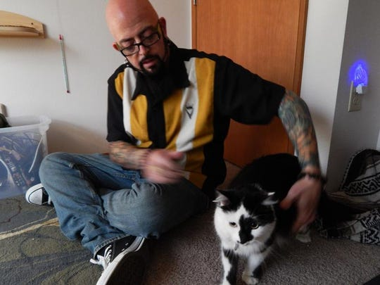 """This undated photo provided by Animal Planet shows Jackson Galaxy, host of Animal Planet's """"My Cat From Hell,"""" with a cat named Lux, in Portland, Ore. If you watched the TV reality show """"My Cat From Hell"""" this past weekend, you saw the feline behaviorist Galaxy trying to tame Lux, a cat that became notorious after its owner placed a 9-1-1 call about Lux attacking the couple's baby and then chasing the family into a bedroom. The show's ending is a cliff-hanger."""