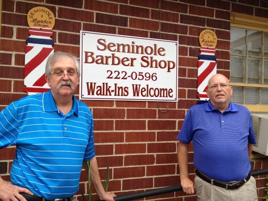Dwayne Edenfield (left) and Larry Creamer stand outside their shop at the corner of Pensacola and Dunwoody in April 2014.