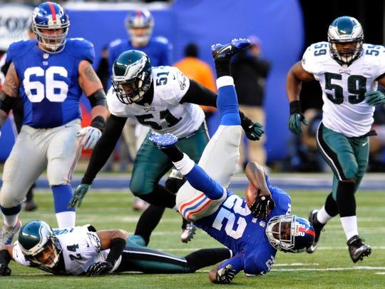Philadelphia Eagles' Jamar Chaney (51) and Nnamdi Asomugha (24) tackle New York Giants running back David Wilson (22) during the Dec. 30, 2012 football game in East Rutherford, N.J.