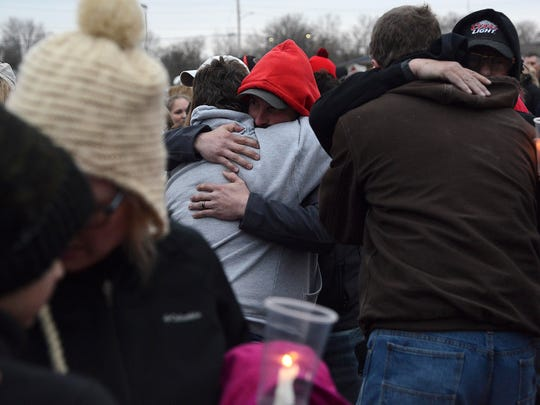 Community members embrace each other Sunday, March 25, 2018,  during a candlelit vigil at the Veterans of Foreign Wars baseball field in Creston, Iowa, in honor of the Iowa family of four found dead Friday,  March 23, 2018, in Mexico.