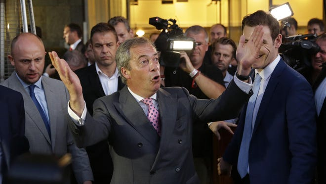 """Nigel Farage, the leader of the UK Independence Party, celebrates and poses for photographers as he leaves a """"Leave.EU"""" organization party for the British European Union membership referendum in London, Friday, June 24, 2016.  (AP Photo/Matt Dunham)"""