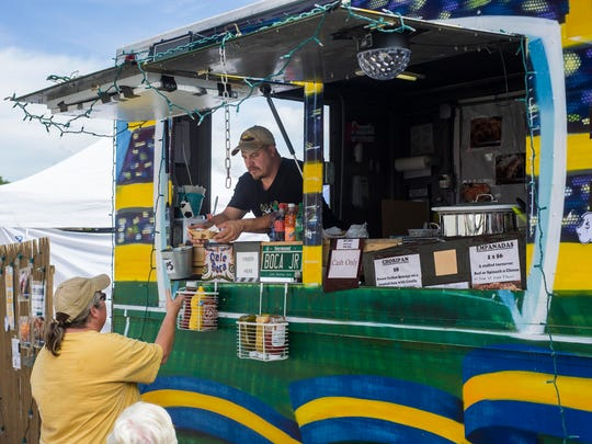 Javier Zirko of Grand Isle serves a customer some Argentinian cuisine from the Dale Boca food truck at the Champlain Valley Fair in Essex on Tuesday, August 29, 2017. Dale Bocca is one of four new food vendors at the fair this year.