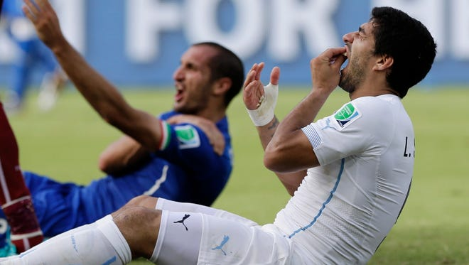 In this June 24, 2014, file photo, Uruguay's Luis Suarez holds his teeth after running into Italy's Giorgio Chiellini's shoulder during a group D World Cup soccer match in Natal, Brazil. Perhaps odder things happened in sports in 2014, but for sheer audacity, and on a global stage no less, the bite by Suarez takes the crown.