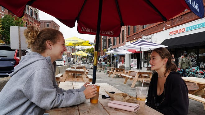 Annabella Haskell, left, and her friend Stella Bolduc, both of Portsmouth, and both waitresses in the city, enjoy drinks outdoors at The Works Bakery Cafe in Portsmouth Tuesday.