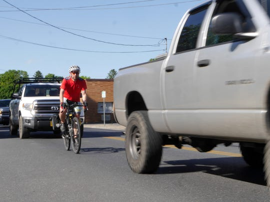Phil Johnson of Staunton commutes on his bike from his job in Verona at Daikin Applied Americas on Friday, May 13, 2016. He was struck by a car on Rt. 11 in front of Ingleside Golf Resort in 2015. Phil Johnson rides with traffic on Spring Hill Road in Staunton Friday, May 13, 2016.