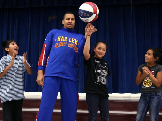 Crockett Elementary Students Fabian Garcia (from left), 11, Lynette Castillo and Layla Bell Saavedra, 10, helps Harlem Globetrotter El Gato Melendez explain the ABCs of preventing bullying to fellow fifth-graders at the school on Monday, October 30, 2017. Students in the BullyProof program at the school graduated from the program Monday.
