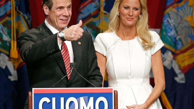 Democratic Gov. Andrew Cuomo gives a thumbs-up to the crowd Tuesday as he celebrates his re-election with his partner, TV chef Sandra Lee, after defeating Republican challenger Rob Astorino, at Democratic election headquarters in New York.
