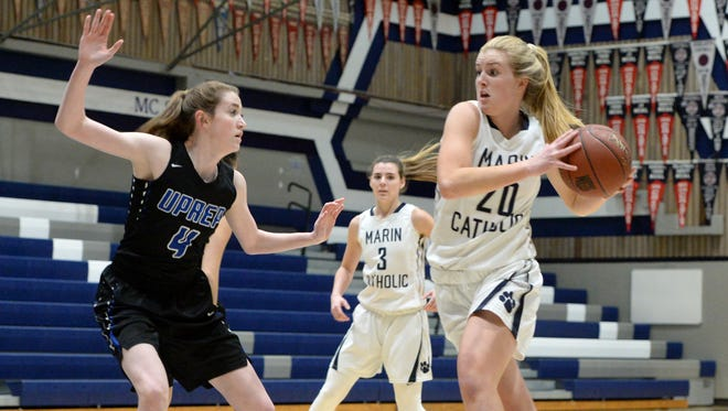 Chase Geffert of Marin Catholic dashes toward the basket as Lauren Anspach of U-Prep defends during their NorCal D-IV playoff game in Kentfield on Wednesday. U-Prep lost 40-36.