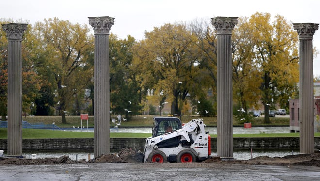 Menasha city employee Dan VanBuskirk works on a downtown riverside park Oct. 24. The park includes limestone pillars from the former First National Bank on Main Street that were carved more than a century ago.