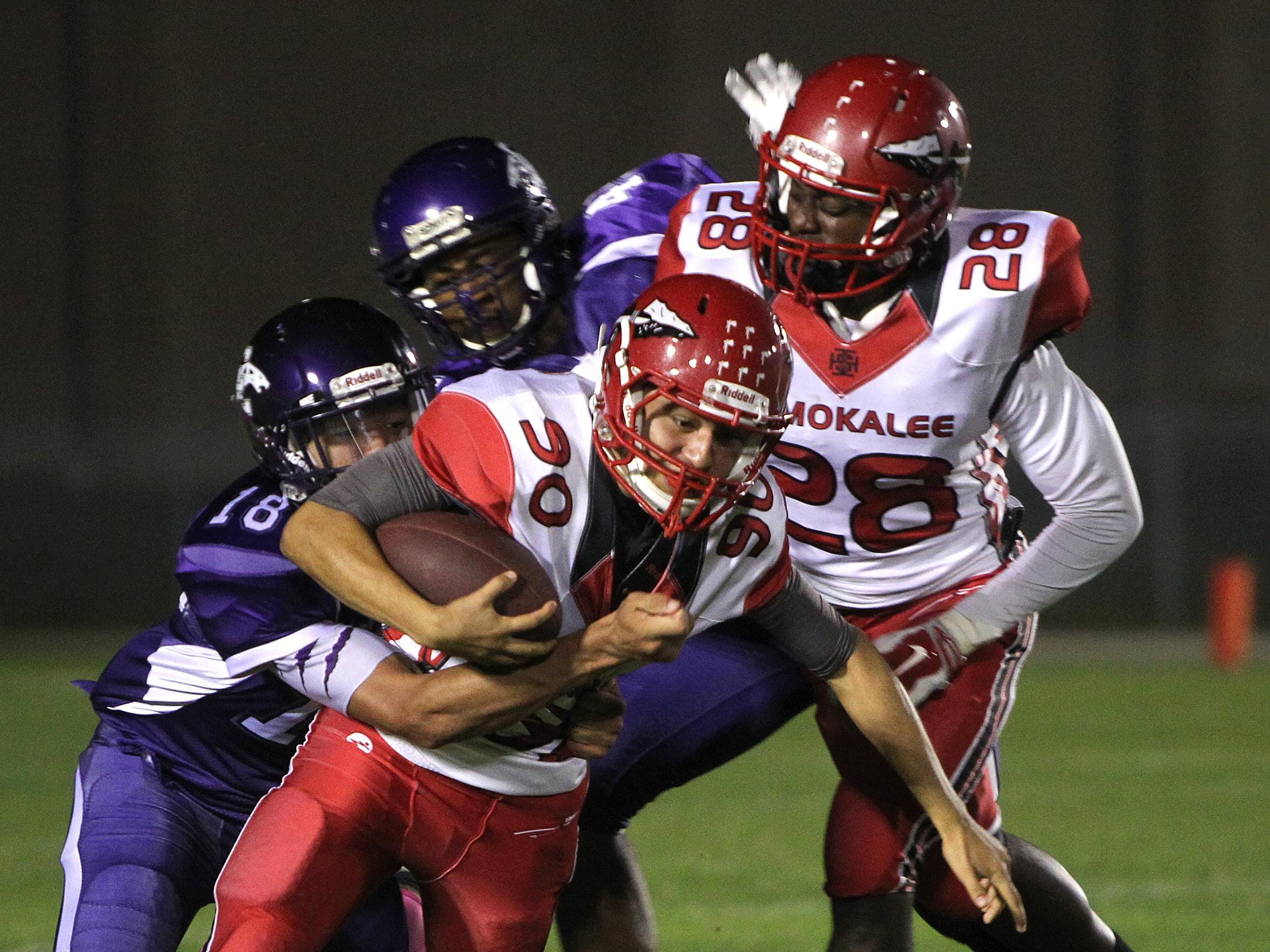 Immokalee ball carrier Elias Cuevas is wrapped up by Cypress lake defender Keyon Brawner while Cypress Lake's Clifford Moore and Immokalee's Terson Jean-Baptiste are in the mix as the Immokalee Indians visit the Cypress Lake Panthers Friday in Fort Myers.