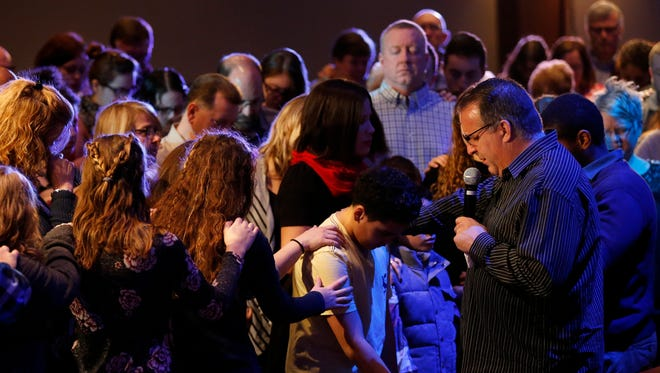 Pastor Mark Ledford invites the congregation to pray over Adrianna Melo and her two sons during the 10:30 a.m. service Sunday, Feb. 11, 2018, at the Church of the Nazarene in Westerville, Ohio. Melo's husband, Raul Melo, is an Ohio State Highway Patrolman based in Columbus.