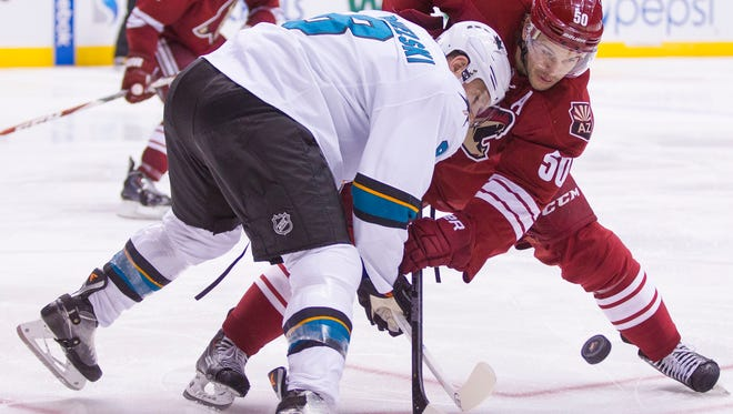 The Sharks' Joe Pavelski and Coyotes' Antoine Vermette (50) face off in the third period at the Gila River Arena in Glendale on Feb. 13, 2015.
