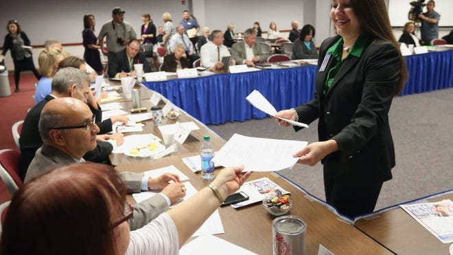 Human Resources Administrator Melissa Morin collects signatures from superintendents from the Coastal Bend after signing an agreement that allows students to take college preparatory courses while in high school to meet college readiness standards Wednesday at the Education Service Center Region 2.