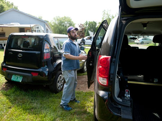 Kevin Robar inspects the handicap accessible fleet of minivans parked outside of Cathy Robar's Colchester home on Thursday July 24, 2014. Big Brother car service formed in the wake of the closure of Benways and Morph Transportation.