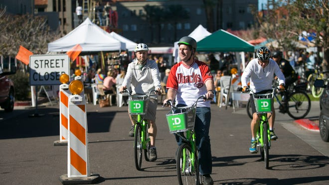 Phoenix Mayor Greg Stanton (center) leads Marc Adams (left), a faculty member with the ASU College of Health Solutions, and Arizona Republic reporter Bob Young (right) on a bike ride using the Grid Bike Share system at the Phoenix Public Market and around downtown Phoenix on Saturday, Jan. 24, 2015.