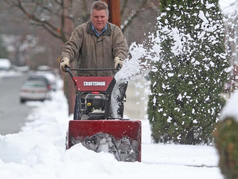 Joe Samluk uses a snow blower out to clear his driveway in Wilmington, Del., on Dec. 9,  2013.