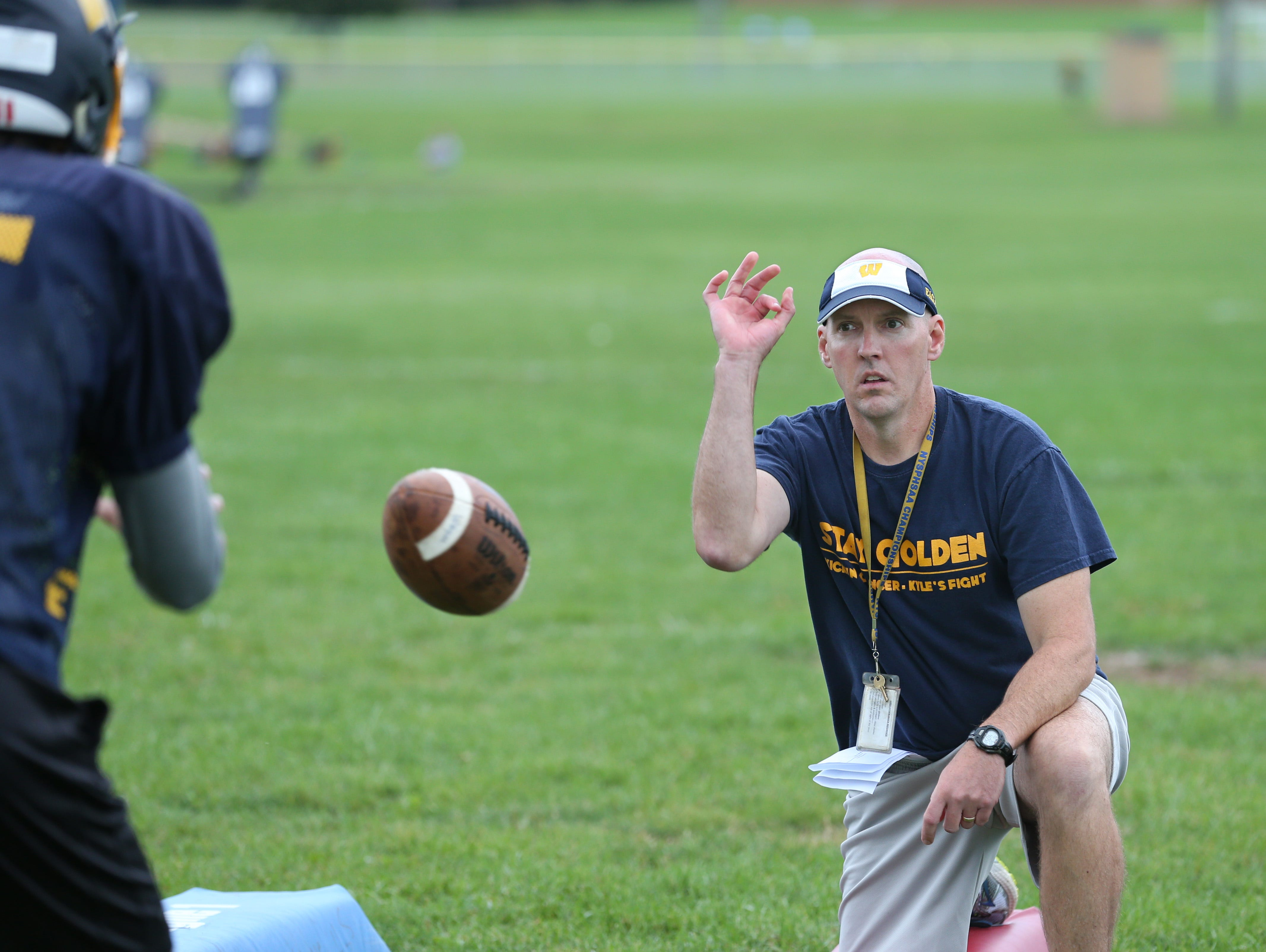 Wayne varsity football head coach David Marean snaps the ball to his quarterback Braeden Zenelovic, as the offensive unit runs through plays during the team's practice at Wayne Central School in Ontario Monday, Sept. 28, 2015.